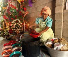 Mujer salvadoreña junto a olla con frijoles rojos, tortillas y arreglo floral. Foto de LPG