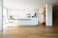 Auf der einen Seite der Kühlschrank mit eingebauten Geräten, auf der anderen Seite eine Garderobe mit Kleiderstange, Beleuchtung, Sitzgelegenheit und Schubladen.   Lass auch Du dich inspirieren - Dein bautrends.ch - Inspirationsteam . . #küche #weisseküche #garderobe #kochinsel #küchenidee #kücheninspiration #bautrends #bautrendsch #elbau Table, Furniture, Home Decor, Kitchen Seating, Kitchen Inspiration, Custom Kitchens, Cabinet Drawers, Room Decor, Home Interior Design