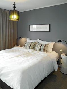 Veggen er malt i skyggeblå fra Jotuns Pure Color. Vegg-til-vegg-teppet Fletco sisallike fra interiorkupp.no og lange, tette gardiner fra Ikea skaper hotellfølelse på soverommet. Taklampen er fra Habitat, bordlampene fra Ikea og nattbordene fra Kartell.