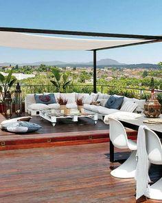 Une pergola pour créer un salon sur la terrasse en bois, avec banquettes et table basse en palettes // White pergola on the terrace