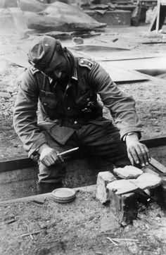 thebeautyandthehorror:A German Army sergeant roasting bread on a small fire, Stalingrad, Russia, Nov 1942.