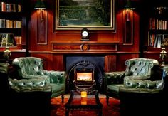 Wood library walls, mossy green tufted club chairs, green tole lamp, brass sconces with green shades