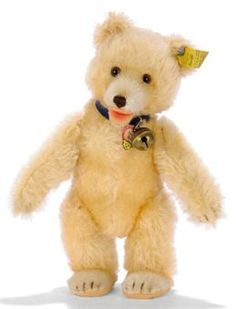 A STEIFF POST-WAR TEDDY BABY, (2322,00), maize mohair, brown and black glass eyes, shorter mohair muzzle and feet, brown stitching, open felt mouth, swivel head, jointed limbs, felt pads, inoperative squeaker, blue leather collar with bell, grey painted FF button with yellow cloth tag, chest tag and US-Zone tag in seam, 1950s --8¾in. (22cm.) high (slightly faded)