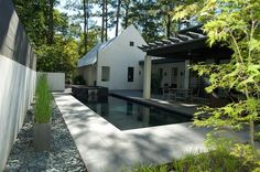 This pool feels mysterious and appears deeper than it is, becoming the focal point of the space and balancing the dark pergola above. Dark-b...