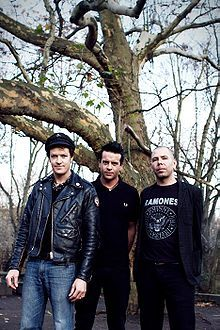 Three men stand in front of a bare tree. All are shown in three-quarter body shot and facing forward. Man at left is tallest, he has dark hair and wears a dark cap, a dark leather jacket which is unzipped, and blue jeans. He holds his arms along his sides. Middle man is slightly shorter, with dark clothes and his arms behind his back. He is partly behind and obscured by first man. Third man is shortest, his head hair is very short and sparse and his hands are behind his back. He wears a dark…