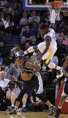 Golden State Warriors' Nate Robinson, top, kicks Memphis Grizzlies' Marreese Speights in the head as he hangs from the basket during the second half of an NBA basketball game Wednesday, March 7, 2012, in Oakland, Calif.