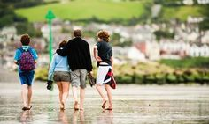 A family on holiday, walking on the sandy beach at Borth, on the Cardigan Bay coast, Ceredigion, Wales, UK
