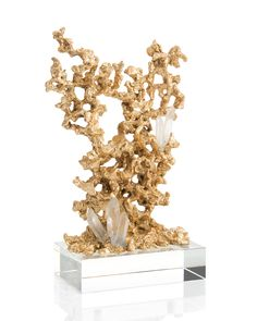 A very organic cast brass sculpture cradles several large quartz points. They all sit atop a crystal base.