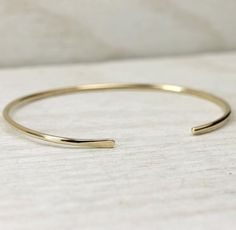 These simple and modern 14K yellow solid gold cuff bracelets are perfect on their own or with any other piece. These cuffs are just under 2mm across and are bot