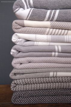 A collection of NEUTRAL HOUSE grey and black hamam towels to bring in a bit of colour to this predominantly grey bathroom.
