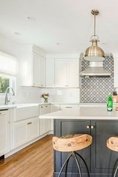 Black and white kitchen with pops of gold #kitchenideas #kitchenremodel #kitchenislandideas #kitchenislandseating #goldlighting #lightfixtures #backsplash #pattern