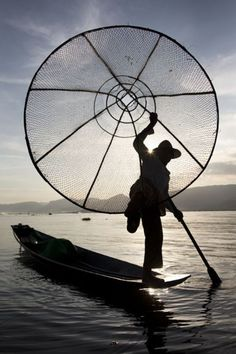 """""""A Burmese fisherman rests at the point of his boat on an ..."""