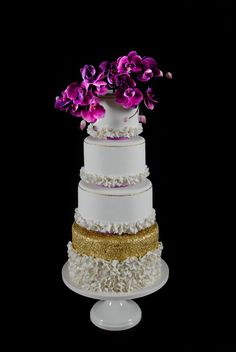 Towering Radiant Orchid wedding cake.  Masterfully handcrafted sugar orchids top this towering sophisticated gem.  Created by cakeglam.com