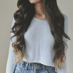Beautiful brunette waves with blonde tips. White cropped top and high-waisted shirts.
