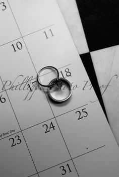 """Wedding rings on a calendar or that day's newspaper. Cute pic. Could maybe try it as a """"save the date"""" with the engagement ring on the day of the wedding... :)"""