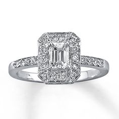 A stunning emerald-cut diamond is the focal point of this beautiful engagement ring. Round diamonds frame the center for added sparkle. Additional round diamonds are set in 14K white gold. The total diamond weight of this fine jewelry ring is one carat. Diamond Total Carat Weight may range from .95 - 1.11 carats.