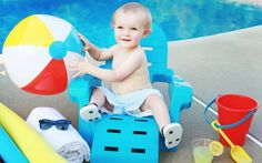 Baby boy first birthday photo shoot. By the pool beach ball themed!