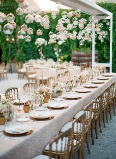 Glass spheres of roses and candles add interest and light above long tables ~ http://www.stylemepretty.com/destination-weddings/france-weddings/2016/10/17/green-salmon-glamorous-destination-provence-wedding/