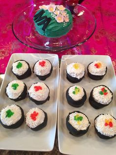 """Sushi roll cupcakes. Cherry chip cake mix - cupcake tin. Black fondant strips rolled out for seaweed wrap.  White frosting with white sprinkle """"pearls"""" Cut up gummy bears for the tops."""