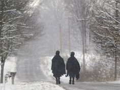 Amish girls walking along a quiet road on a snowy day in Ohio