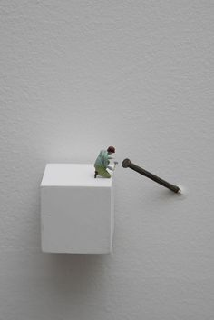 """Liliana Porter """"Forced Labor (Nail)"""" Figurine on wooden base and nail on wall 2008 Contemporary Sculpture, Contemporary Art, Miniature Calendar, Minis, Sweet Station, Miniature Photography, Wall Installation, Art Installations, Tiny World"""