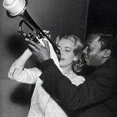 Miles Davis giving Jeanne Moreau a trumpet lesson.