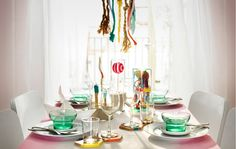 A table laid with dinnerware and decorated with pastel colored beach finds.