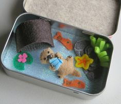 This is my sweet baby Otter miniature felt Altoid tin play set. The otter measures just 1 1/2 tall from the top of his head to the tip of his little tail. Hes made from felt, carefully stuffed with polyester fiberfill and detailed with embroidery floss. In his little paws hes holding an