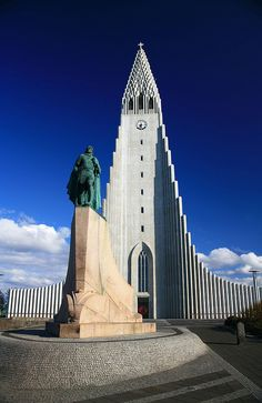 Hallgrímskirkja and Leifur Eiríksson, Iceland - [Hallgrímskirkja is perhaps the most famous church in Rejkjavík. The statue in front of the church is of Leifur Eiríksson, perhaps the most famous person from Iceland (after Björk, that is). Beautiful Architecture, Beautiful Buildings, Beautiful Places, The Places Youll Go, Places To Visit, Iceland Island, Iceland Travel, Reykjavik Iceland, Interesting Buildings
