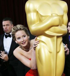 """Jennifer Lawrence, best supporting actress nominee for her role in the film """"American Hustle"""", peeks around an Oscar statue on the red carpet as actor Brad Pitt looks on at the Academy Awards in Hollywood, California March REUTERS/Adrees Latif. Jennifer Lawrence Oscar, Jenifer Lawrence, Brad Pitt, Ellen Degeneres, Mtv, Vietnam Tour, Vietnam Travel, J Law, Best Actress"""