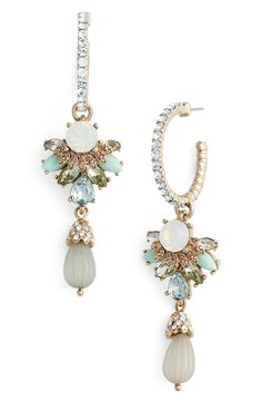 Slender pavé-crystal-encrusted hoops get a regal boost from clusters of dazzling jewels and dangling beads that sway from these statement-making earrings.