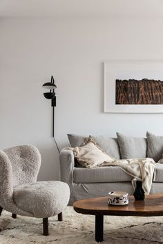 A cosy Nordic living room designed by Blooc with a grey linen sofa and fluffy Little Petra chair by &Tradition. #nordicdesign #&tradition #neutralinteriors #livingspace #livingroomdecor #linensofa #viggoboesen #littlepetra