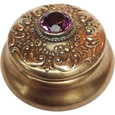 Sterling box with amethyst colored stone and silver scrolling design on the lid. It has a gold wash that has faded on the exterior. These Victorian