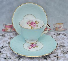 Vintage bone china tea trio made by English china maker Aynsley, likely manufacture date 1950s- 1960s. The tea trio consists of tea cup, saucer, tea plate in duck egg blue with a pink rose on the interior of the cup and centre of the plate. The china is gilded to the rims, foot and handle of the cup and also a circle of gilt to the centre of plate and saucer. The china is textured to resemble the veins of flower petals and this has become known as crocus design. The china is in excellent…