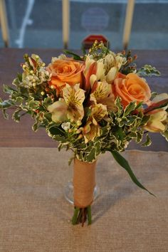 Rustic Charm Bridesmaid Bouquet. A smaller bouquet to compliment the Rustic Collection Bridal Bouquet.  This bouquet is composed of orange roses, peach alstromeria, ivory waxflower, and edged with delicate variegated mini pittosporum.  Wrapped with your choice of double-faced satin ribbon or burlap and lace and pearl or crystal pins.