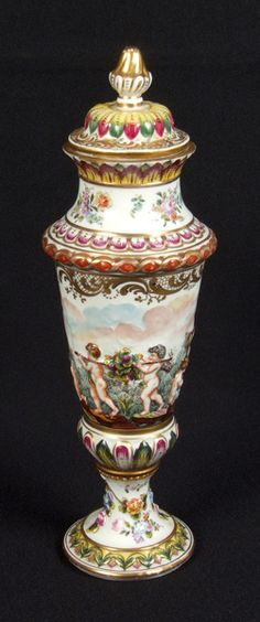 CAPODIMONTE LIDDED URN. Capodimonte porcelain lidded urn decorated with a frieze of putti displaying artistic talents of painting, sculpting, flower arranging and grape gathering. Urn also decorated with garlands of flowers