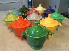 All 11 vintage Fiesta sugar bowls.  Front to back: medium green, red, yellow, chartreuse, gray, original green, turquoise, rose, cobalt, forest green, ivory!