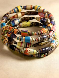 Paper bead bracelet using glossy magazines and varnish. I want to have a go at making these. Would work well as a gift using a favourite magazine. I'd also like to experiment with rounder beads, not sure how yet, watch this space!