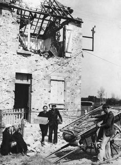 Family leaving the ruins of their home in Carentan, 1944.
