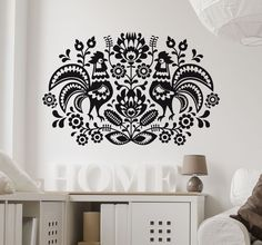 A wall sticker with a beautiful symmetrical design of ornate floral patterns and two hens. Ideal for adding a decorative touch to any room.  This mono-colour design is inspired by traditional polish folk art and is the perfect touch to transform plain and boring walls! Choose from over 50 colours and match it perfectly with the rest of your decor. Delicate floral sticker that can compliment any room from bedroom to living room. #Floral #Bedroom #Decoration