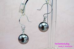 This pair of earrings is simple, yet with superb quality.  The large Tahitian pearl of this pair of earrings, measuring 14 mm, is a shell pearl. Its color is Silver with a hint of Pink.