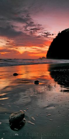 Sunrise reflection, Pololu Beach, Hawai'i. The main road on the north shore of the Big Island is 270 and it abruptly dead-ends at the cliffs of the Pololu Valley. From this vantage point you can easily view the half-mile long black sand beach that lies below. (V)