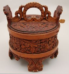 Round container of stave construction. Staves are held together by two one-inch birch bands. Four extended staves form the feet, and two extending at top form the support for the flat cover. All exterior parts are gracefully and masterfully carved with acanthus style leaves and florals.    Marks: Eldrisvalsdatter (?) Syvergaard 1861 painted on bottom. E.S.D.S. (?) 1861 painted on inside cover.    Garmo family brought the ambar to western North Dakota sometime before 1892
