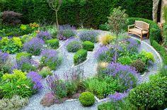 gartengestaltung bilder, runder hintergarten mit naturstein und vielen pflanzen und blumen