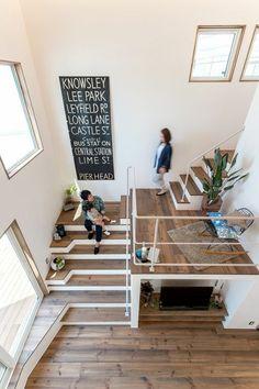 escalier bois PVC avec garde corps en métal blanc, inscription sur tableau noir fixé au mur blanc, étage de mansarde