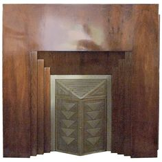 French Art Deco Fireplace Mantel. Modernist design from the 30s.  Hardwood corpus, with French walnut veneer.  Metal doors in relief, stamped and hammered geometric pattern. Marble top.