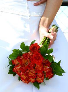 Un ramo de novia muy especial con rosas rojas con tono degradado acompañado con follaje verde.