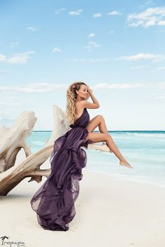 Incredibly beautiful blond girl with curly hair in amazing purple dress sitting on the old huge branch at the beach in front of the aquamarine ocean #dress #beach #fashion