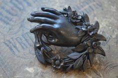This amazing little mourning brooch is made so beautifully! It features a hand grasping a wreath made of leaves and flowers, with a very