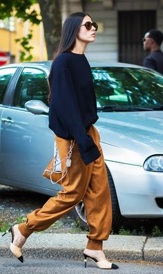 A navy jumper worn with burnt orange silk trousers, Chanel heels, and sunglasses